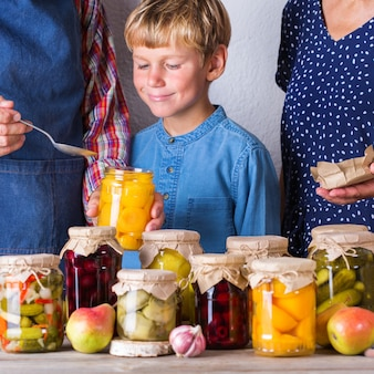 Casal idoso com neto degustando compota de frutas para preservação