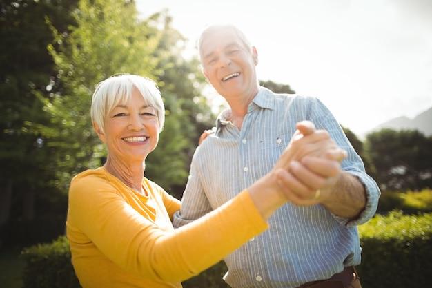 Casal idoso dançando no parque