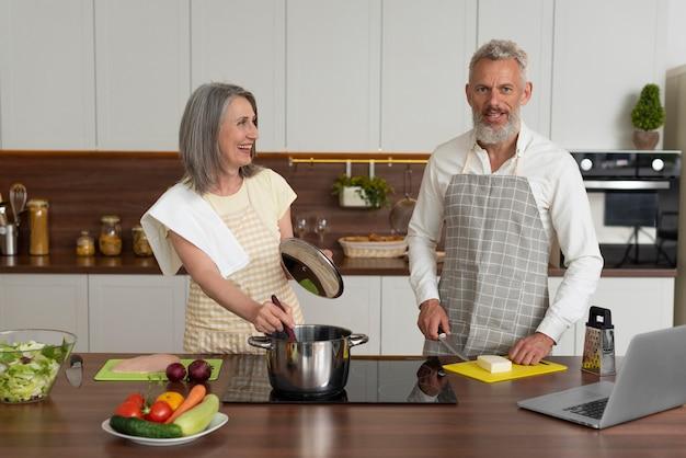 Casal idoso em casa na cozinha tomando aulas de culinária no laptop