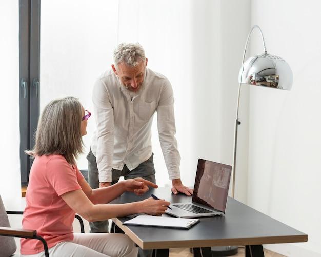 Casal idoso em casa usando laptop