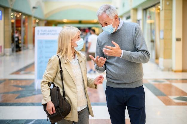 Casal idoso fazendo compras em um shopping na época do coronavírus, usando máscaras