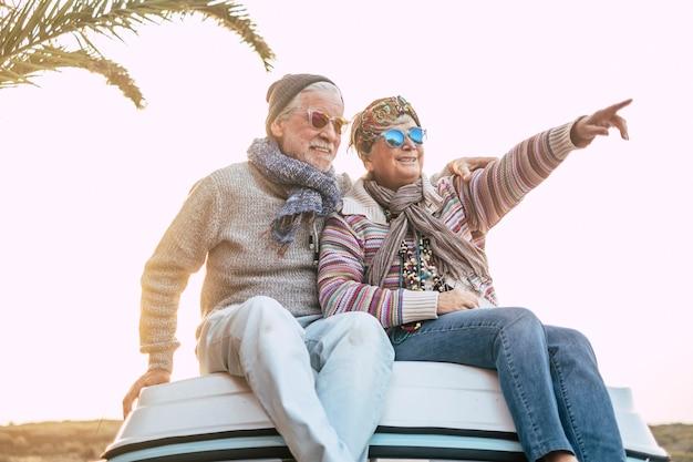 Casal idoso feliz e jovem desfrutam juntos a viagem e a alegria do estilo de vida sentados no teto da van