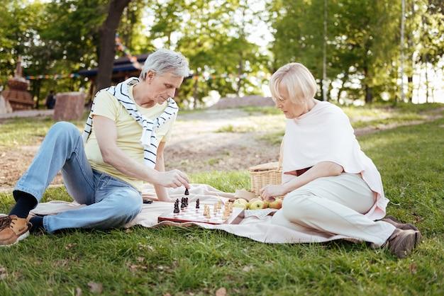 Casal idoso inteligente envolvido expressando interesse enquanto joga xadrez e faz um piquenique ao ar livre