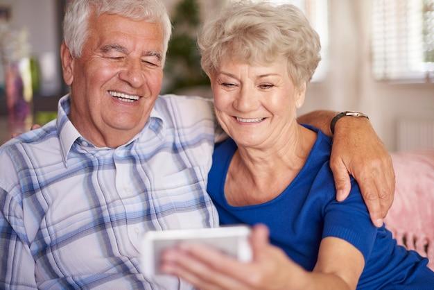 Casal idoso moderno tirando uma selfie