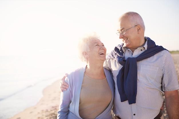 Casal idoso na praia, aposentadoria e conceito de férias de verão