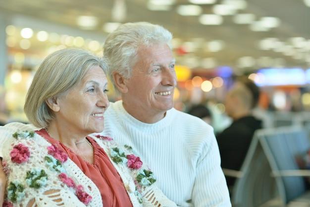 Casal idoso no aeroporto sentado no banco