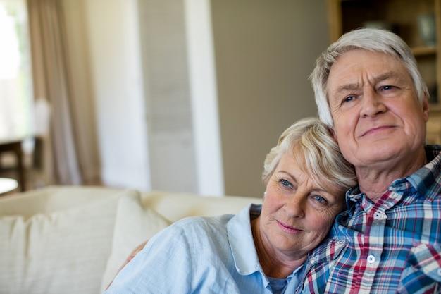 Casal idoso sentados juntos no sofá