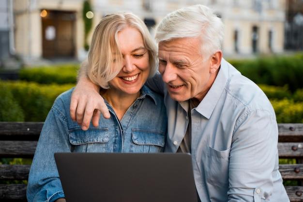 Casal idoso sorridente abraçado ao ar livre com laptop