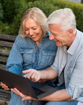 Casal idoso sorridente ao ar livre com o laptop no banco