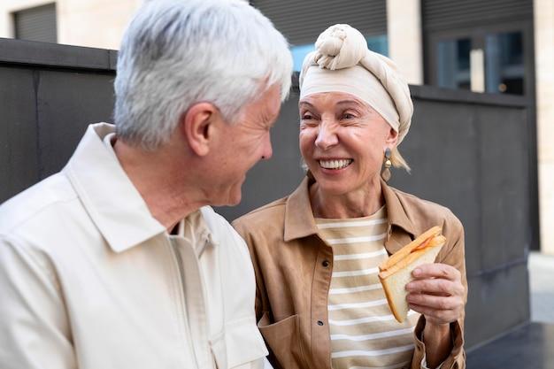 Casal idoso sorridente ao ar livre comendo um sanduíche juntos