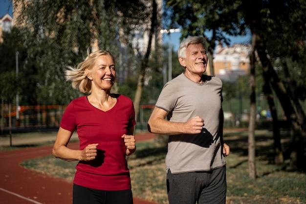 Casal idoso sorridente correndo ao ar livre