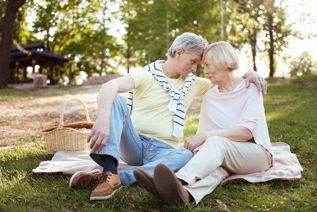 Casal idoso sorridente e harmonioso expressando felicidade enquanto se abraça e desfruta de um piquenique ao ar livre