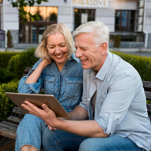 Casal idoso sorridente olhando para um tablet na cidade