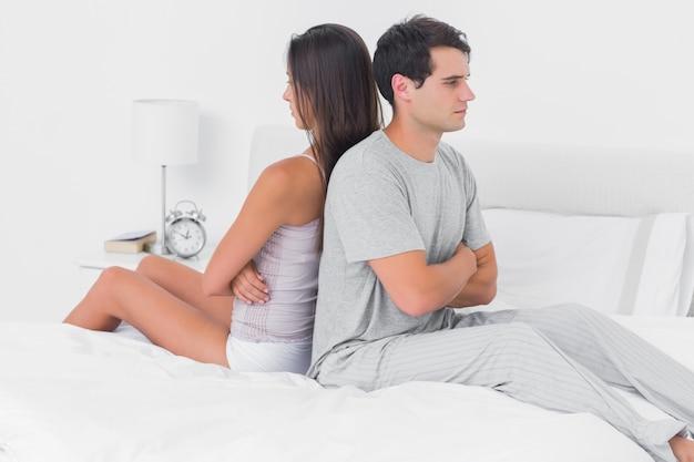 Casal ignorando-se sentado de costas para trás na cama
