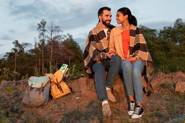 Casal improvisado sentado nas pedras olhando um para o outro