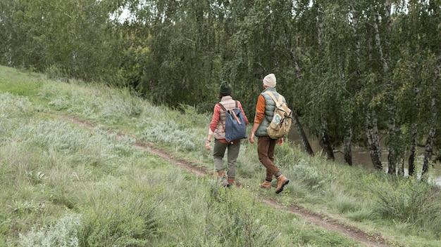 Casal improvisado subindo uma trilha