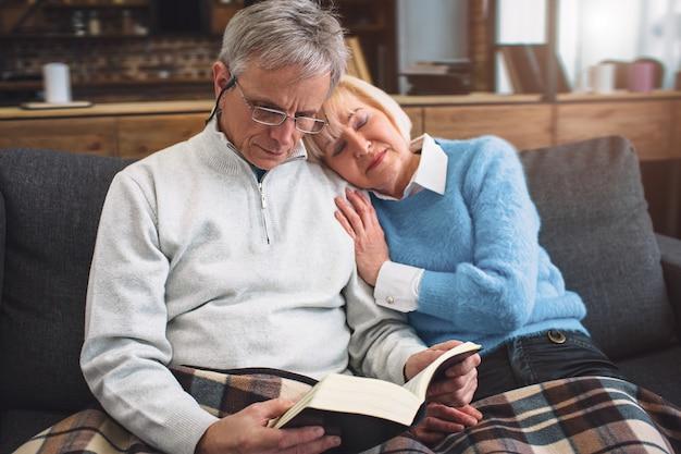 Casal incrível e agradável estão sentados juntos em uma sala. homem está lendo