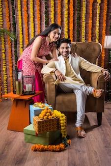 Casal indiano atraente com roupas tradicionais comemorando o festival, aniversário ou aniversário de diwali com presentes surpresa e doce laddoo contra um fundo decorado com flores de calêndula