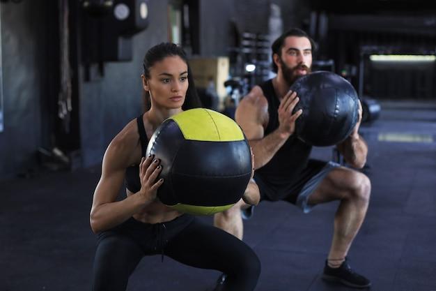 Casal indiano atraente fazendo fitness com bola medcine no ginásio.
