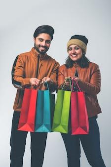 Casal indiano com sacolas de compras no inverno usa roupas quentes como pano de fundo