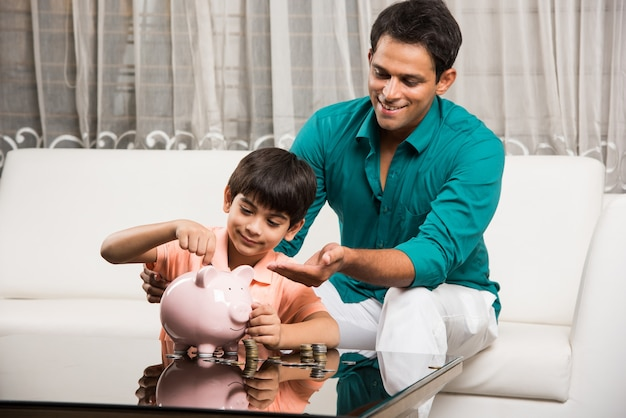 Casal indiano esperto e asiático ensinando a importância de economizar para as crianças em casa com o cofrinho