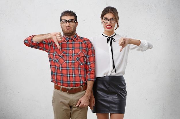 Casal infeliz de professores profissionais mostra sinal negativo, mantém o polegar para baixo, discorda de algo.