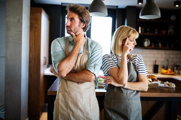 Casal infeliz discutindo e brigando na cozinha que leva ao divórcio