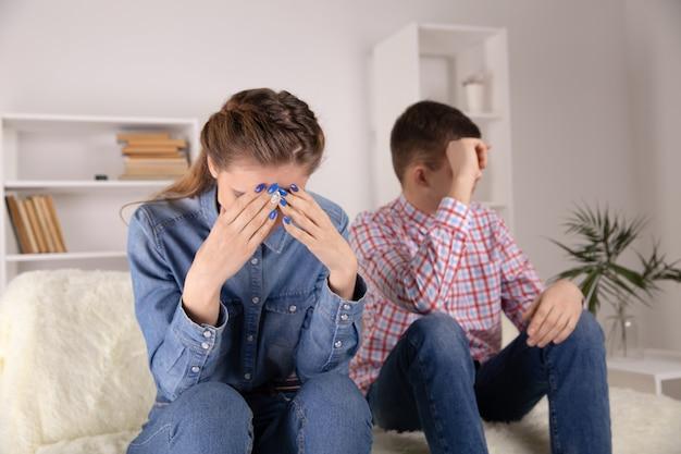 Casal infeliz em estresse. homem triste e mulher sentada no sofá.