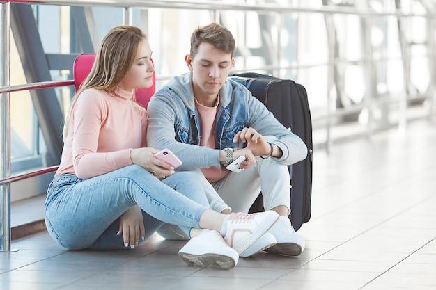 Casal infeliz esperando no aeroporto seu voo atrasado. os jovens perderam o trem. homem e mulher no aeroporto.