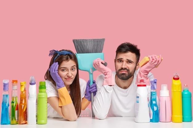 Casal infeliz faz a limpeza da casa juntos, tem expressões de cansaço, usa produtos e materiais de limpeza