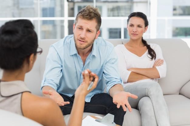 Casal infeliz na sessão de terapia com o homem falando com terapeuta