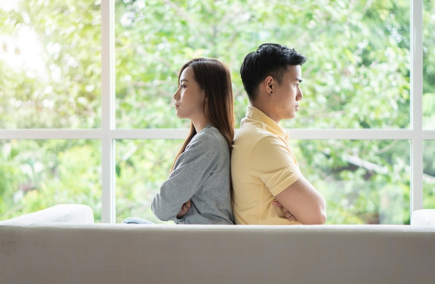 Casal infeliz sentado atrás do outro no sofá e evitar falar ou olhar um para o outro