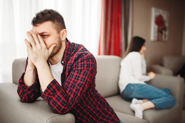Casal infeliz sentado no sofá, conflito familiar. homem infeliz e mulher em briga