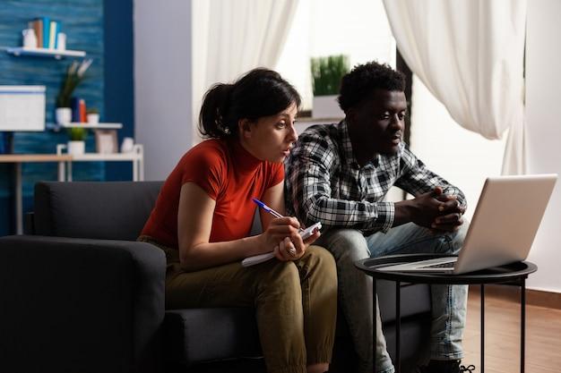 Casal inter-racial calculando dinheiro de impostos usando um laptop
