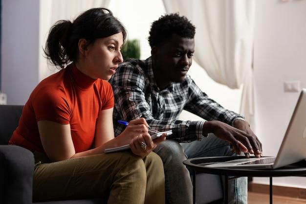 Casal inter-racial calculando dinheiro de impostos usando um laptop Foto Premium