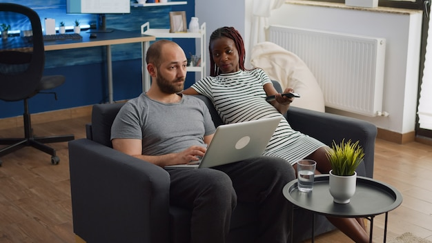 Casal inter-racial com gravidez relaxando juntos em casa