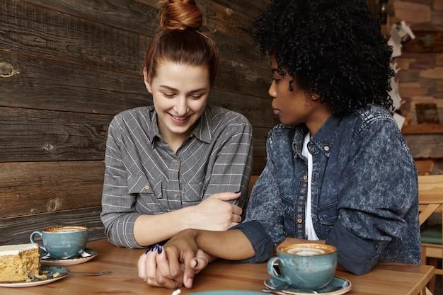 Casal inter-racial de lésbicas olhando para baixo com um sorriso tímido, de mãos dadas durante o almoço em restaurante