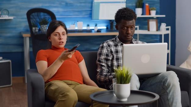 Casal inter-racial esperando um filho sentados no sofá