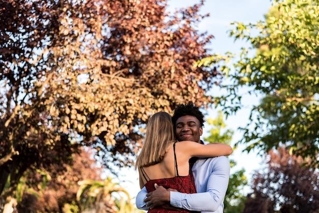 Casal inter-racial se abraçando. menino negro abraçando uma garota caucasiana.