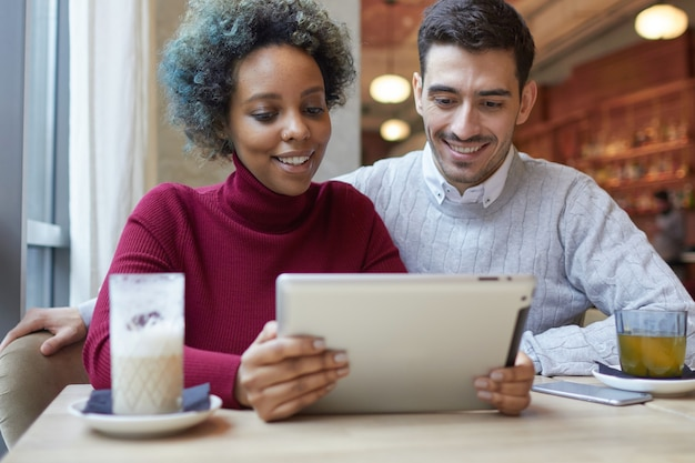 Casal inter-racial sentado em um café e assistindo a um vídeo ou fazendo uma videochamada com um tablet