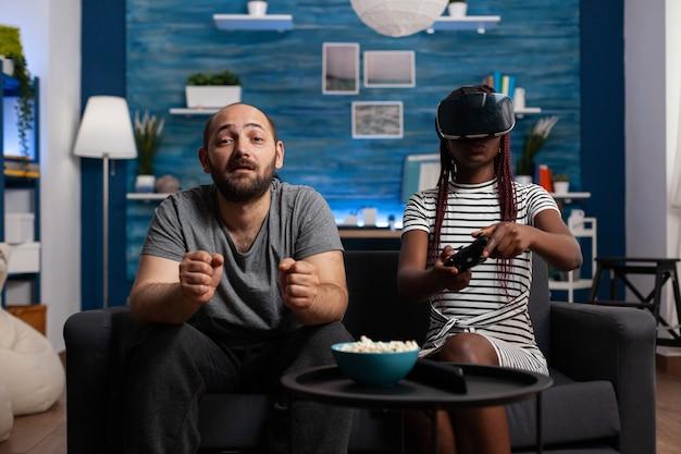Casal inter-racial usando óculos e controladores vr para se divertir