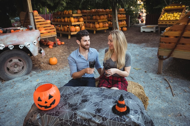 Casal interagindo enquanto toma um copo de vinho