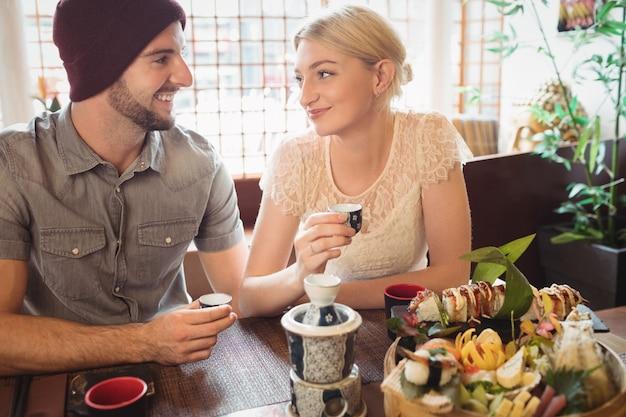 Casal interagindo um com o outro enquanto tomando chá