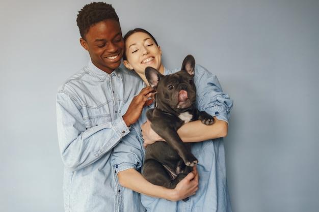 Casal internacional em um fundo azul com um cachorro