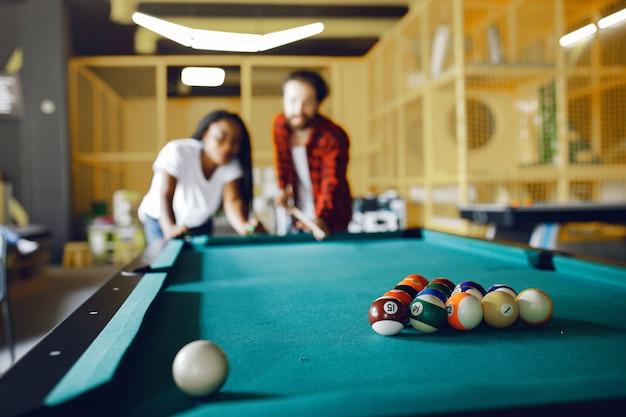 Casal internacional jogando bilhar em um clube