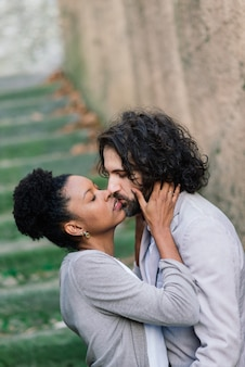 Casal interracial adulto jovem em uma praia, homem branco e mulher afro-americana com roupas casuais em uma praia, dia dos namorados