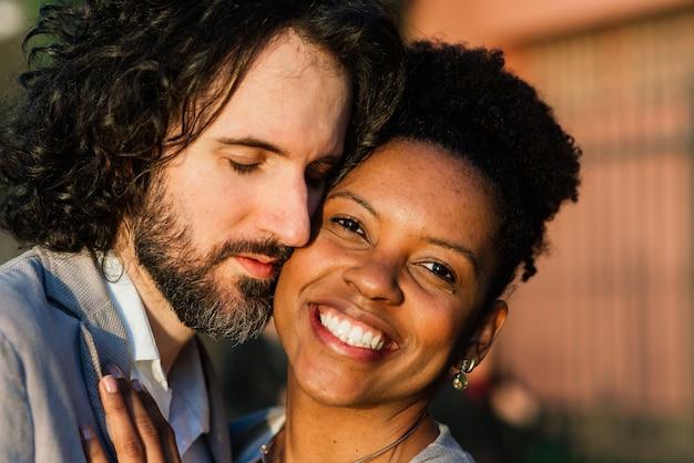 Casal interracial adulto jovem em uma praia, homem branco e mulher afro-americana em roupas casuais, aproveitando o dia de verão na costa do mar