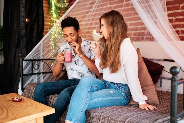 Casal interracial apaixonado bebendo um coquetel em um bar exclusivo