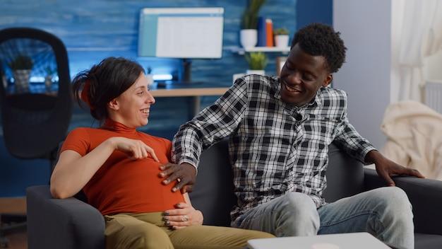Casal interracial casado esperando um filho sentado em casa