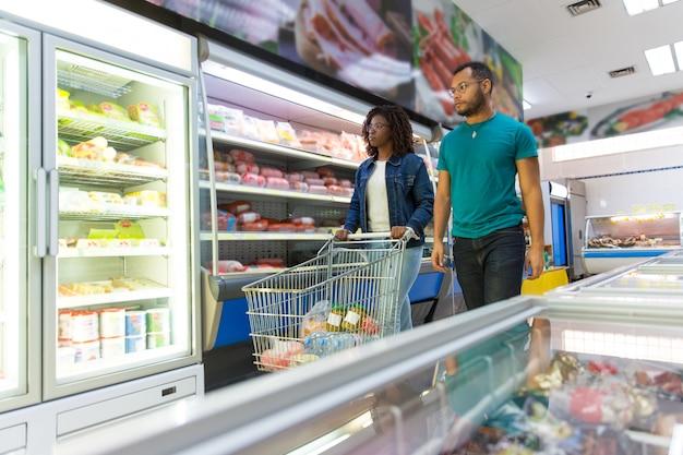 Casal interracial de clientes comprando comida juntos